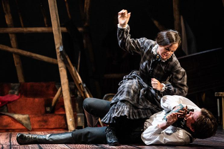 Man and woman in period drama costume. The woman is attacking the man on the ground.